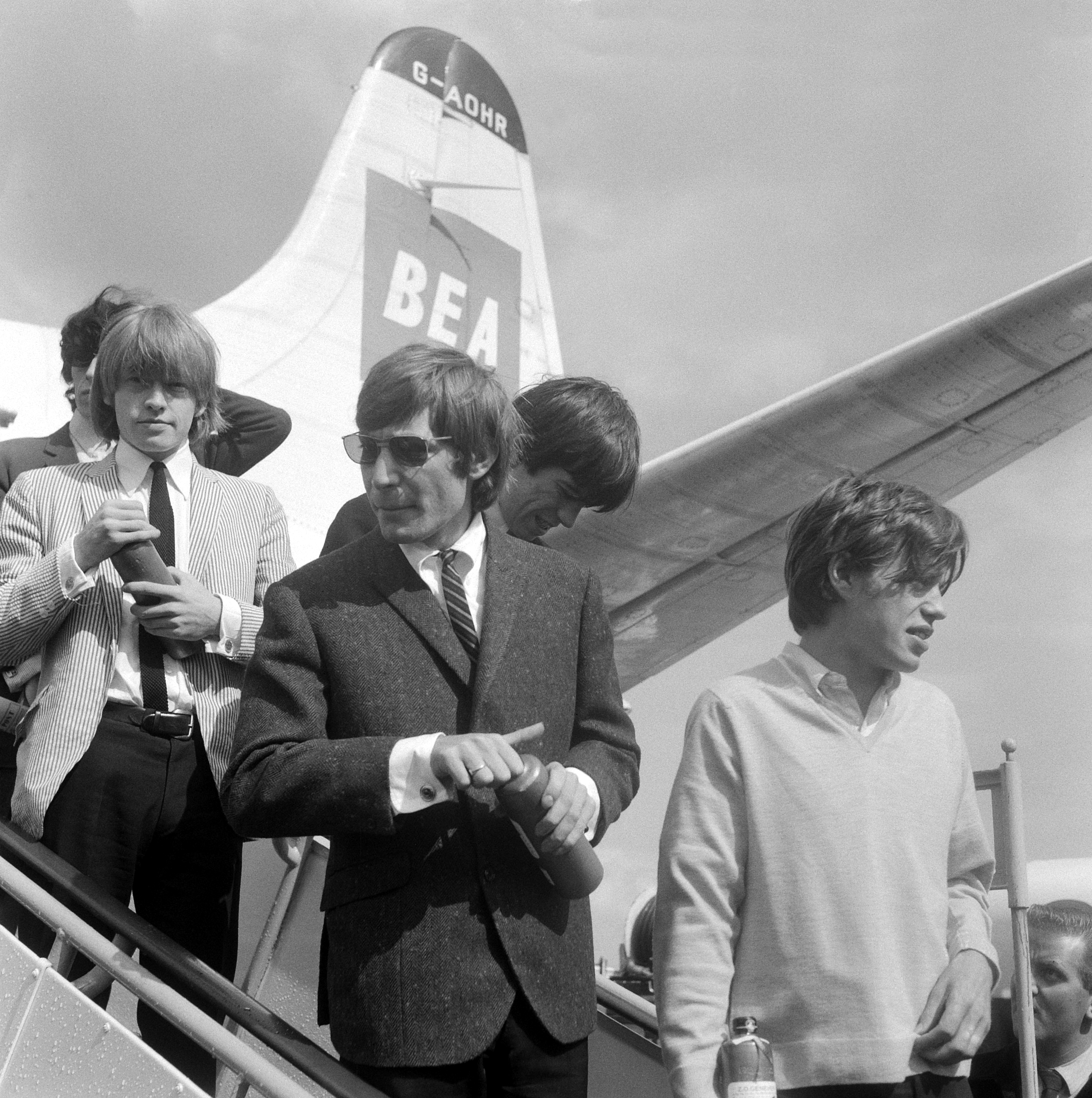 The Rolling Stones getting off an airplane at Airport Schiphol on August 8, 1964. This is a retouched (removed scratches and spots, adjusted colors) version of the image from the Nationaal Archief